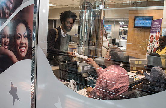 Customer receiving note from an employee at a bank