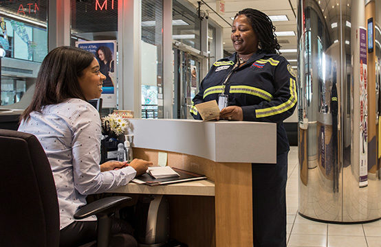 Credit union employee helping a customer standing at her desk