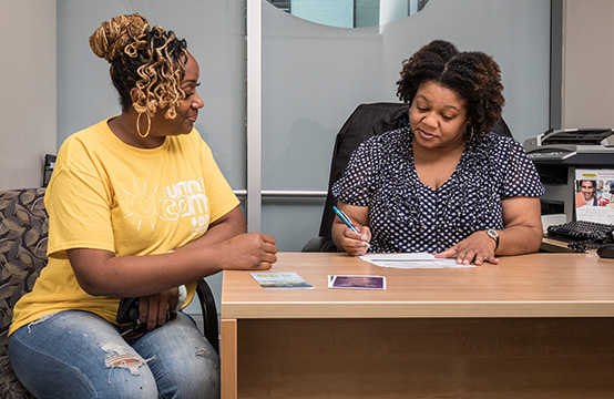 Two women sitting at an office table,signing documents